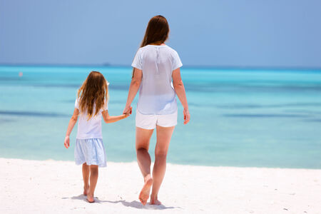 Mother and daughter enjoying tropical beach vacation photo