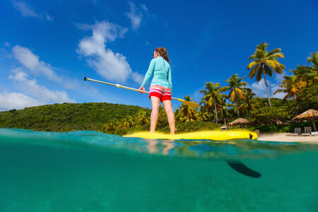 people in action: Split underwater photo of active young woman on tropical beach vacation paddling on stand up board Stock Photo