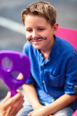 cuteness: Portrait of a cute little boy with mustache painted on his face