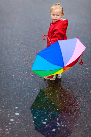 Toddler girl with colorful umbrella on rainy day, beautiful reflection on puddle photo