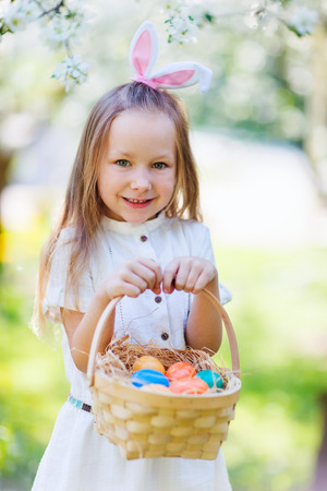 bunny ears: Adorable little girl wearing bunny ears playing with Easter eggs in a blooming garden on spring day
