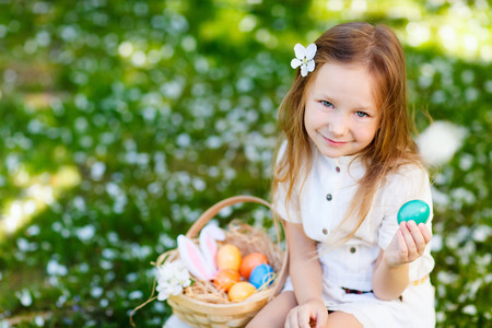 bunny ears: Above view of adorable little girl wearing bunny ears playing with Easter eggs on a grass covered with white flower petals on spring day