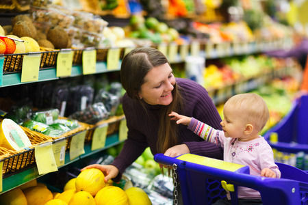 supermarket trolley: Mother and baby daughter in supermarket buying fruits and vegetables Stock Photo