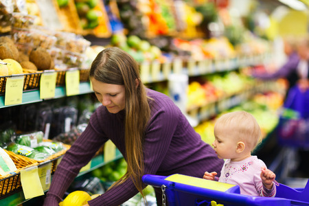 mom: Mother and baby daughter in supermarket buying fruits and vegetables Stock Photo