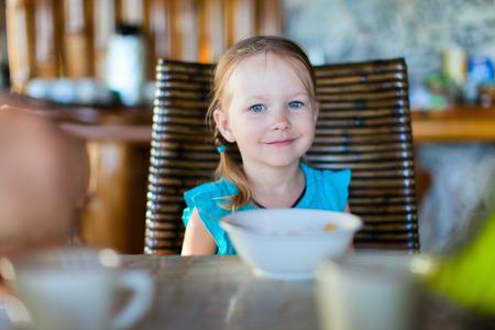 comiendo cereal: Ni�a adorable que come cereal con una leche para el desayuno en el restaurante