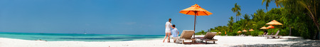 Romantic couple on a tropical beach during honeymoon vacation, wide panorama perfect for banners photo