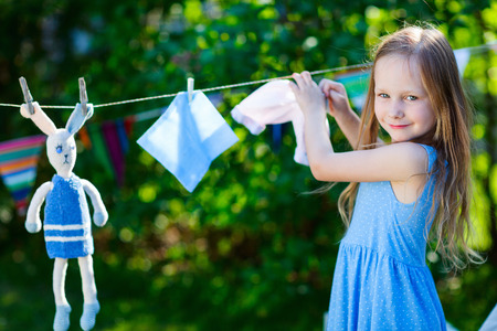 role play: Adorable little girl having fun playing outdoors on summer day
