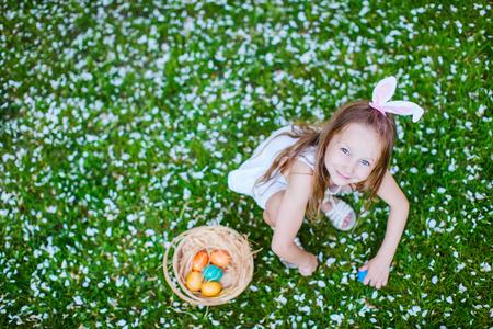 봄 날에 흰색 꽃 꽃잎으로 덮여 잔디에 부활절 계란 재생 사랑스러운 작은 소녀 토끼 귀를 입고의보기 위 스톡 콘텐츠