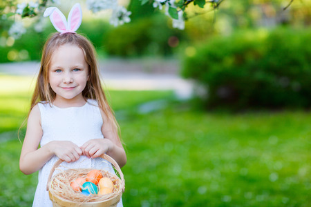 Adorable little girl wearing bunny ears holding a basket with Easter eggs in a blooming garden on spring day