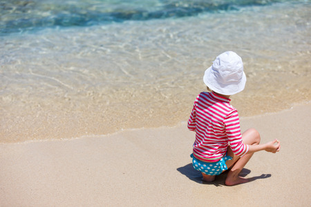 sun protection: Little girl in a colorful sun protection swimwear on vacation at tropical beach Stock Photo