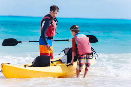 fun activity: Father and son kayaking at tropical ocean