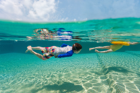 swimming underwater: Split above and underwater photo of adorable kids having fun swimming at pool on summer vacation