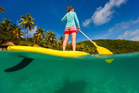 split up: Split underwater photo of young woman on tropical beach vacation paddling on stand up board