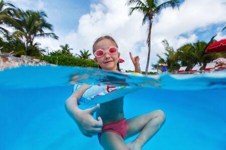 aquapark: Adorable little girl at swimming pool having fun during summer vacation