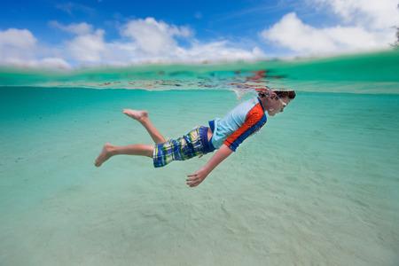 little boy swimming: Cute little boy swimming underwater in tropical sea