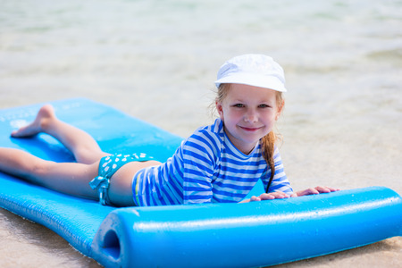 sun protection: Little girl in a colorful sun protection swimwear on vacation swimming on floating mat in a shallow water at tropical lagoon Stock Photo