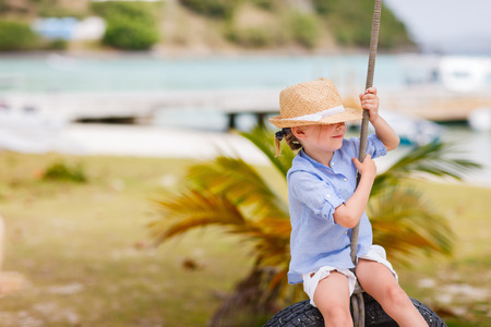 girl on swing: Adorable little girl having fun on tire swing on summer day Stock Photo