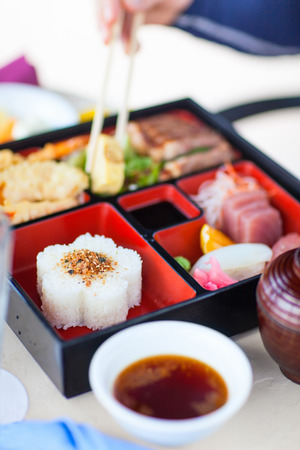bento: Delicious Japanese lunch bento box with rice, fish sashimi, omelet, meat and vegetables