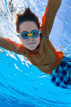 Söt pojke under vattnet i poolen