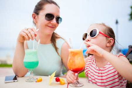 mocktail: Happy mother and her adorable little daughter at outdoors cafe drinking tropical juice