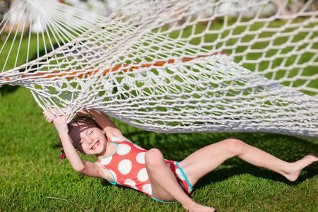 columpios: Niña adorable riendo después de caer el amanecer en una hierba de hamaca
