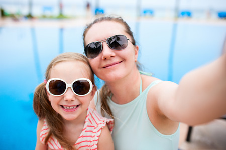 little girl: Happy mother and her adorable little daughter outdoors near a swimming pool taking selfie at tropical resort