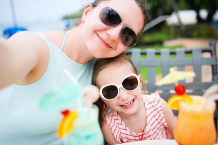 mocktail: Happy mother and her adorable little daughter at outdoors cafe taking selfie while drinking tropical juice