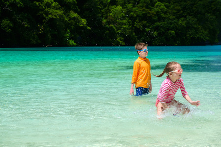 shallow water: Two kids playing at at shallow water during summer vacation Stock Photo