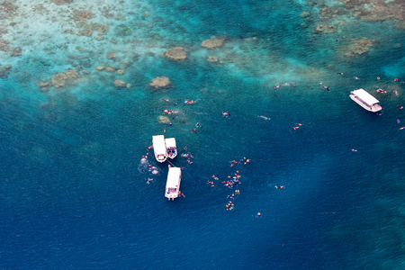 palau: Above aerial view of tropical ocean, boats and tourists snorkelling at reef in Palau