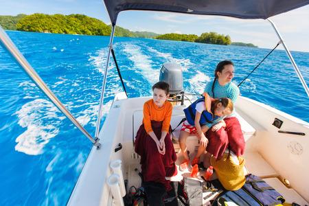 Familj mor och hennes barn på liten båt på privat vatten turné eller utflykt