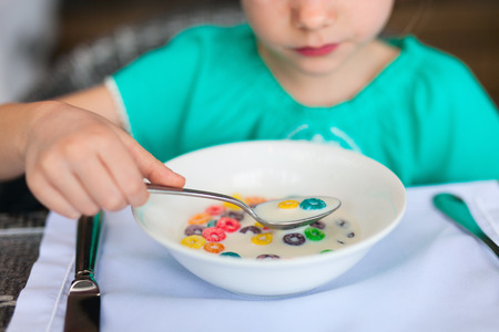 unrecognisable person: Close up of a little girl eating cereal with milk for breakfast in restaurant Stock Photo