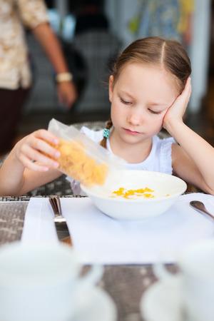 comiendo cereal: Ni�a adorable que come cereal con leche para el desayuno en el restaurante