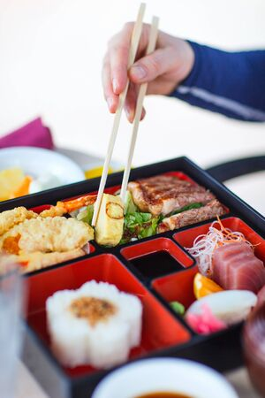 bento box: Delicious Japanese lunch bento box with rice, fish sashimi, omelet, meat and vegetables