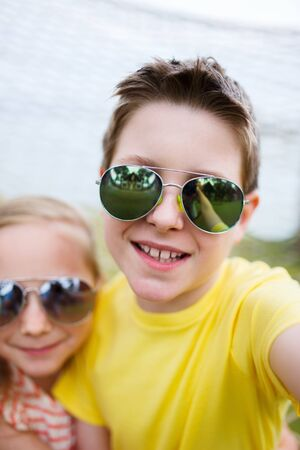 brothers and sisters: Teenage boy taking selfie with his little sister outdoors on summer day Stock Photo