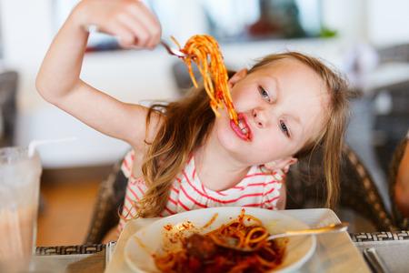 Portrét rozkošné holčička jíst špagety na oběd v restauraci