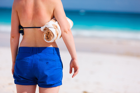 woman back view: Back view of a young woman holding beach towel on tropical summer vacation