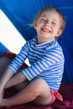 cabana: Little girl at luxury resort relaxing at beach cabana Stock Photo