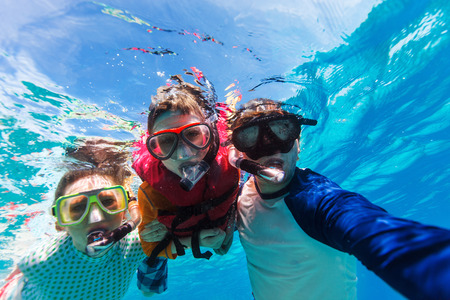 underwater: Underwater portrait of family snorkeling together at clear tropical ocean