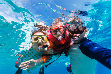 with ocean: Underwater portrait of family snorkeling together at clear tropical ocean