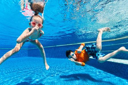 Barn har roligt att spela under vattnet i poolen på semester