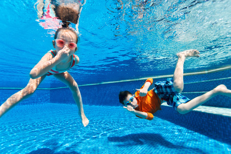 Kids having fun playing underwater in swimming pool on summer vacation