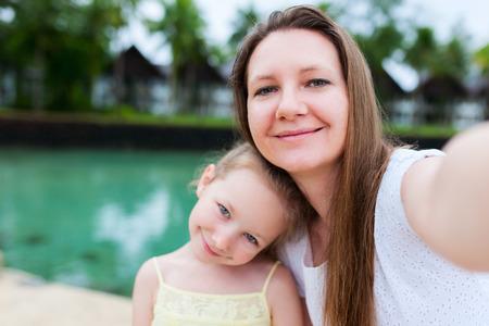 행복 한 가족 어머니와 그녀의 사랑 스럽다 작은 딸이 여름 휴가 셀카를 스마트 폰과 함께 복용