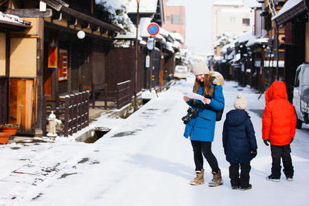 parka: Family of mother and kids at old district of historical Takayama town in Japan on winter day