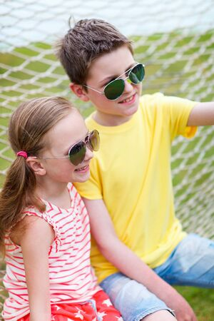 aviators: Teenage boy taking selfie with his little sister outdoors on summer day Stock Photo