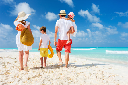 familias jovenes: Vista posterior de una familia feliz en la playa tropical de las vacaciones de verano Foto de archivo