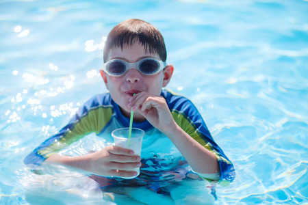 sipping: Cute boy at all inclusive resort swimming pool sipping cocktail Stock Photo