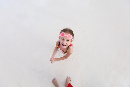 children swimsuit: Top view of adorable little girl at beach during summer vacation Stock Photo
