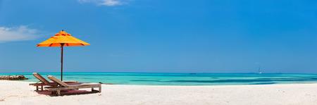 몰디브에서 아름 다운 열 대 해변에서 나무 라운지의 자와 오렌지 태양 우산 스톡 콘텐츠