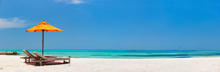 Houten lounge stoelen en oranje parasol op een prachtig tropisch strand op de Malediven Stockfoto