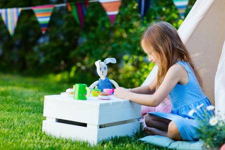tea party: Adorable little girl having fun playing outdoors on summer day